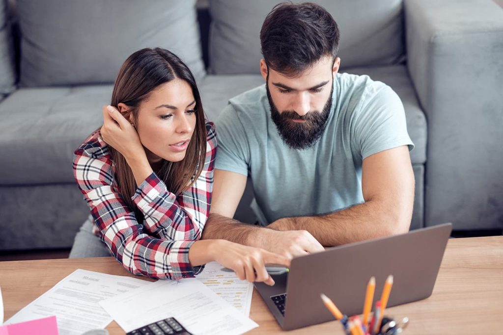 Young couple using a computer,checking bills and paperwork.